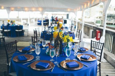 royal blue tablecloths and napkins with orange calla lilies centerpieces