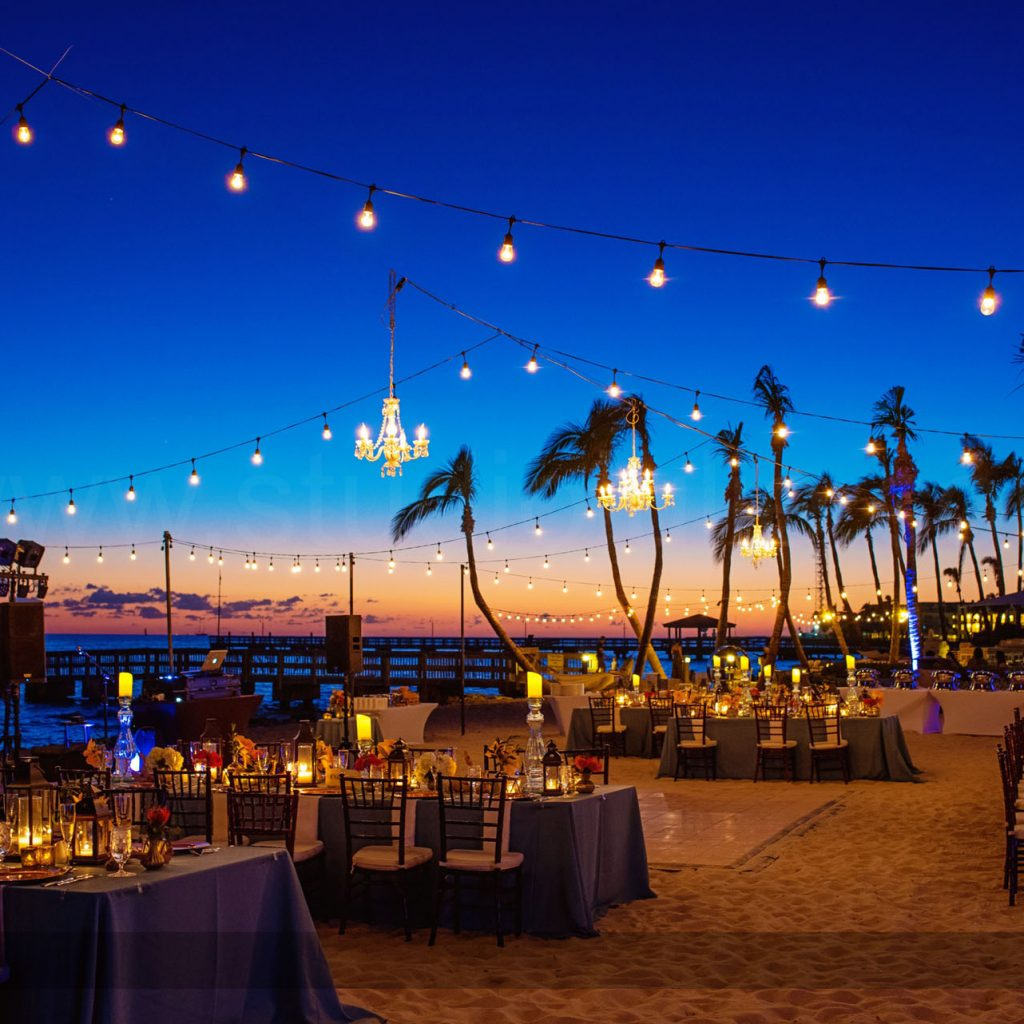 wedding reception with string lights at sunset on the water