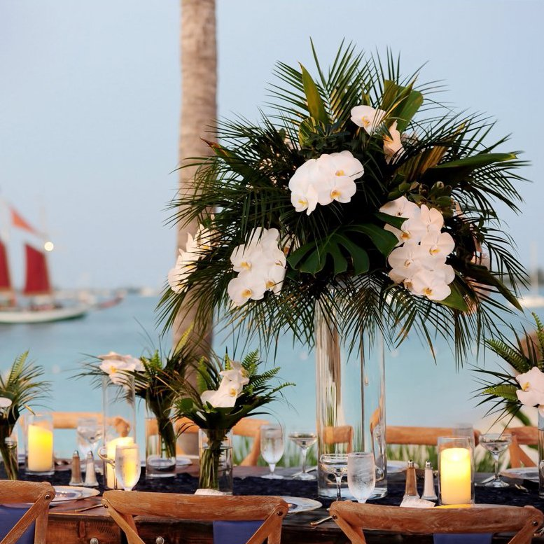 flower centerpiece on a table with a sailboat on the ocean in the background