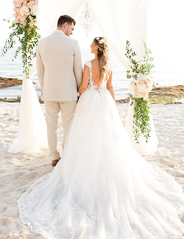 back of a wedding couple on the beach