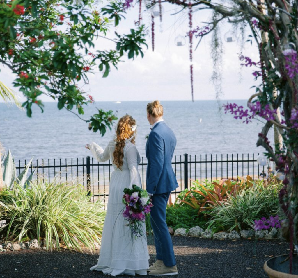 wedding couple surrounded by foliage on the water