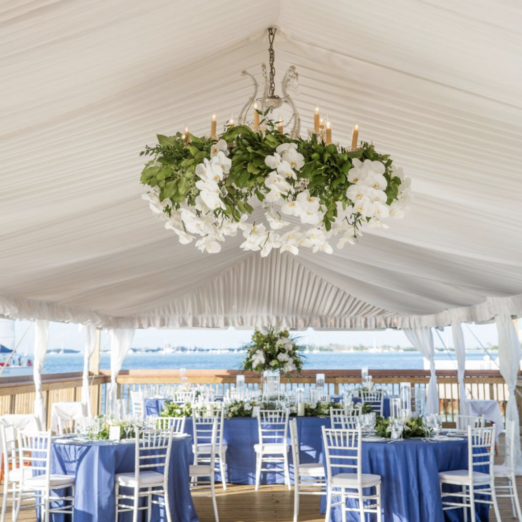 reception tables under a tent with floral chandelier