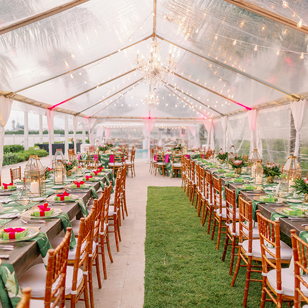 wedding reception tables under a tent with string lighting