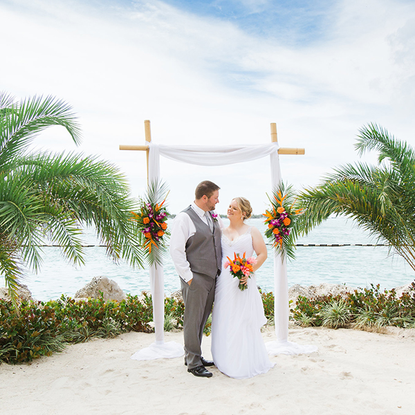 wedding couple on the beach with wedding arch behind them